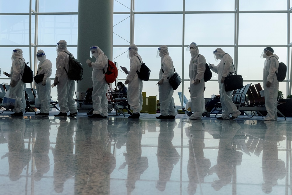 Passengers wearing protective suits (PPE) line up to board their plane for an international flight at Hong Kong airport, July 9, 2021. ― Reuters file pic