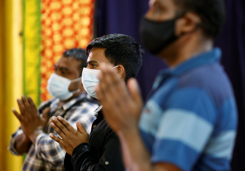 Migrant workers pray at a temple, before enjoying time off at Little India, as part of a pilot programme to allow fully vaccinated migrant workers back to the community in Singapore September 15, 2021. ― Reuters pic