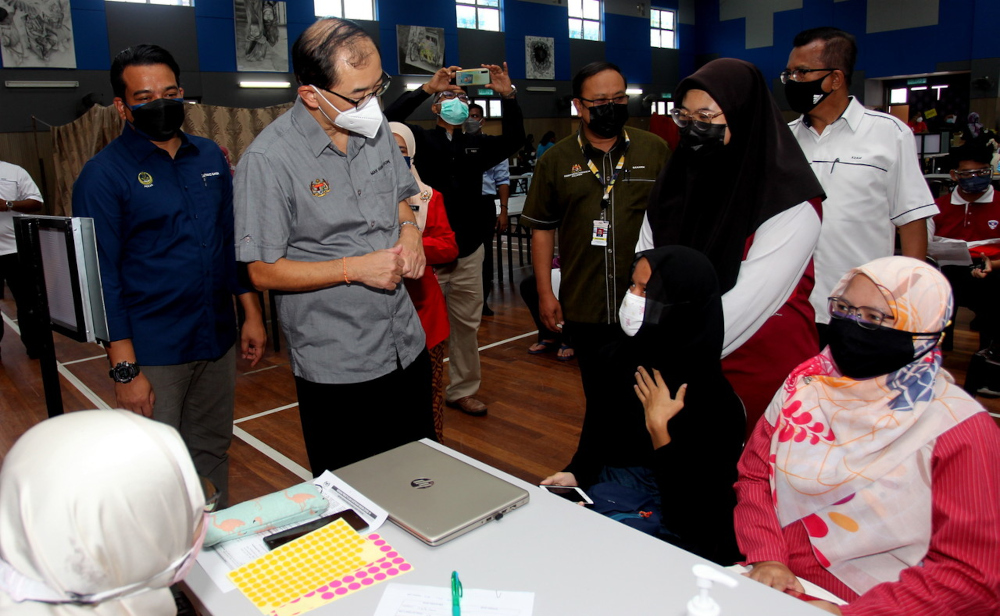 Deputy Education Minister I Datuk Dr Mah Hang Soon speaks to a student at SMK Proton City vaccination centre (PPV) in Tanjung Malim, September 24, 2021. — Bernama pic