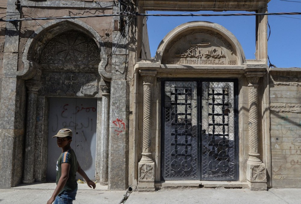 A young boy walks in front of the entrance gate of the Syriac Christian church of Mar Tuma in Iraq's second city of Mosul, in the northern Nineveh province, under restoration on September 14, 2021. — AFP pic