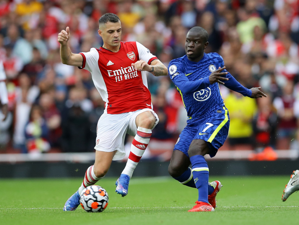 Arsenal's Granit Xhaka in action with Chelsea's N'Golo Kante at Emirates Stadium, London, August 22, 2021. — Reuters pic