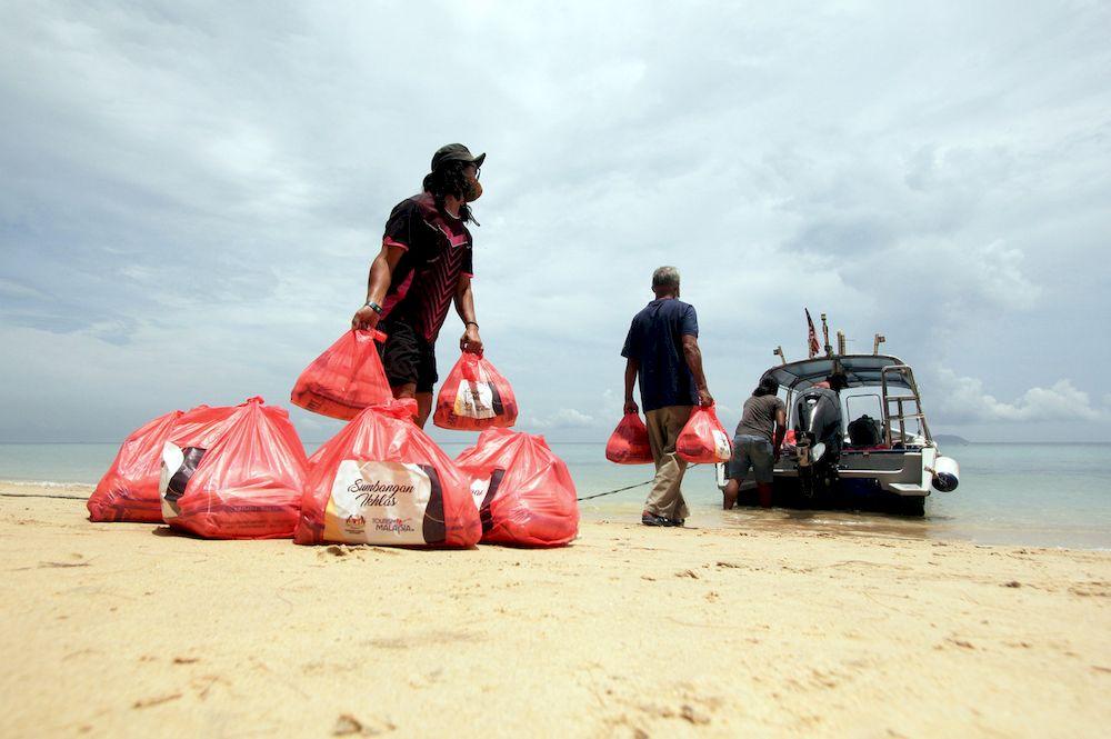 Representatives of food aid recipients loading food baskets into a boat after the donation handover ceremony, in Kampung Tekek, Pulau Tioman, September 6, 2021. — Bernama pic