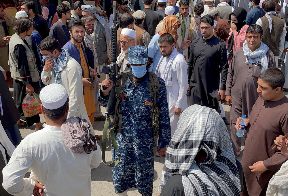 File photo of a member of Taliban security forces standing guard among crowds of people walking past in a street in Kabul, Afghanistan September 4, 2021. — Reuters pic