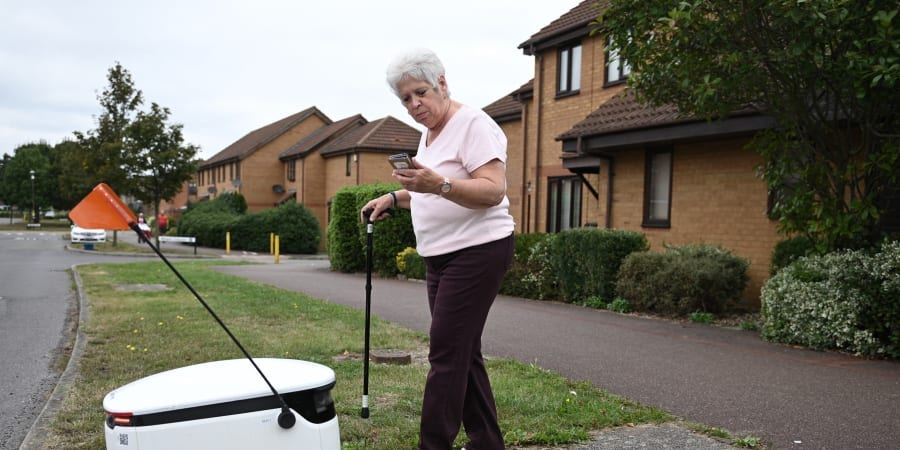 Sheila, 71, accepts a delivery through the app from an autonomous robot called Starship delivering groceries from a nearby Co-op supermarket in Milton Keynes, England. — ETX Studio pic