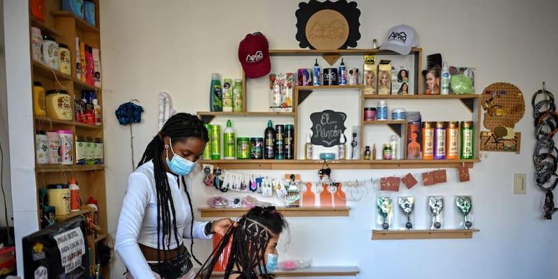 A hairdresser braids a customer's hair at a beauty salon, in downtown Caracas. — ETX Studio pic