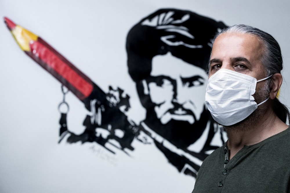 Aghan artist and co-founder of the ArtLords collective, Farshad poses in front of a symbolic drawing of his collective, a Taliban fighter whose rocket launcher is filled with pencils in Paris on September 11, 2021.  — AFP pic