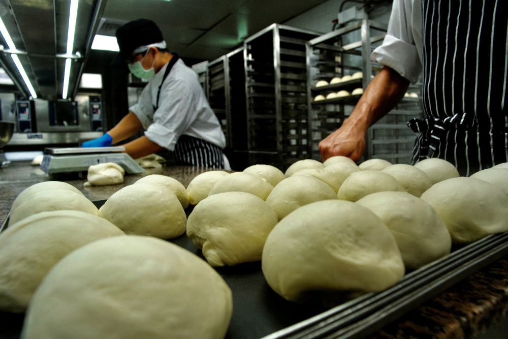 Employees from Taiwan company JustKitchen, a network of 'ghost kitchens' that make delivery-only food, preparing to bake bread for takeaway meals at one of their locations in Taipei. — AFP pic