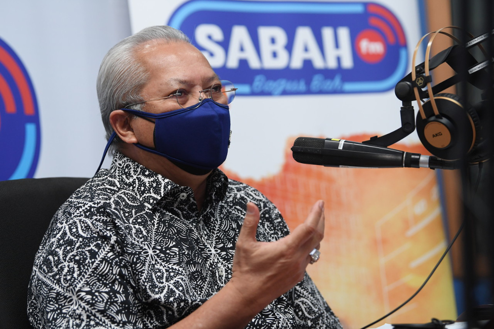 Communications and Multimedia Minister Tan Sri Annuar Musa answers a radio caller's question at the Ministry of Communications and Multimedia's Integrated Complex in Kota Kinabalu, September 16, 2021. — Bernama pic