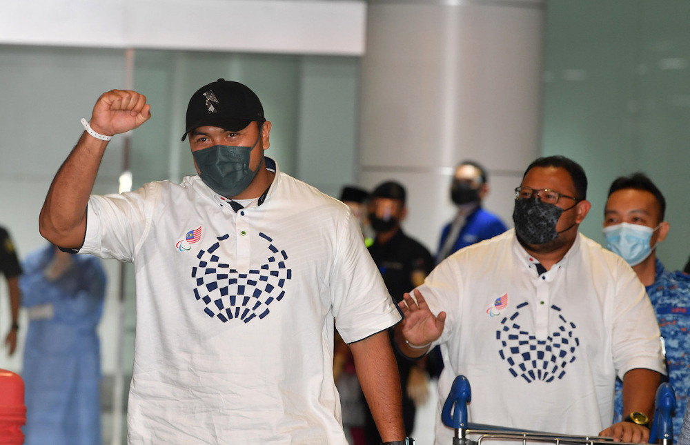 Malaysia's Muhammad Ziyad Zolkefli (left) and his coach arrive at KLIA after their return from the 2020 Tokyo Paralympics September 3, 2021. — Bernama pic