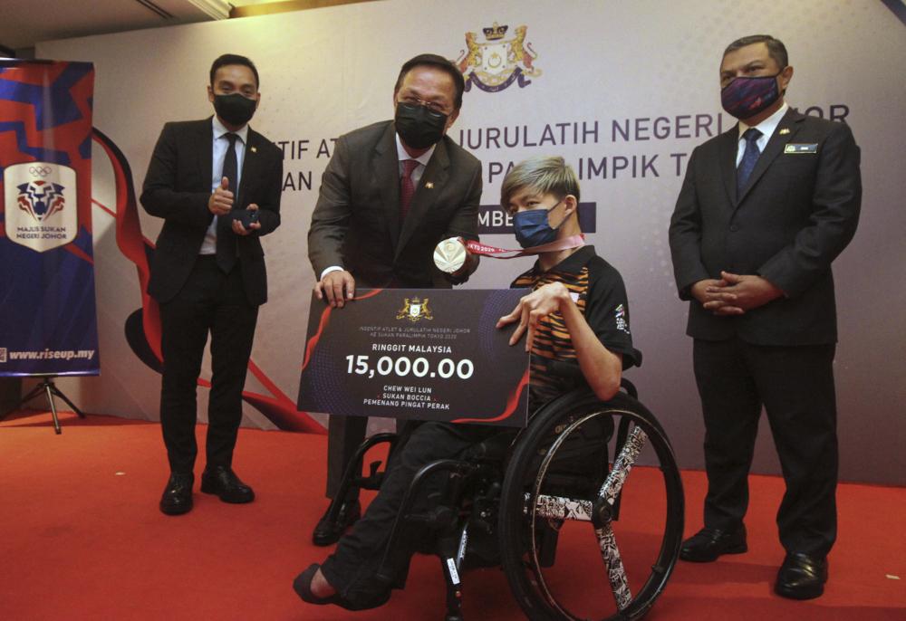 Mentri Besar Datuk Hasni Mohammad hands the incentive to Tokyo 2020 Paralympic Games silver medallist Chew Wei Lun in Johor Baru, September 21, 2021. — Bernama pic