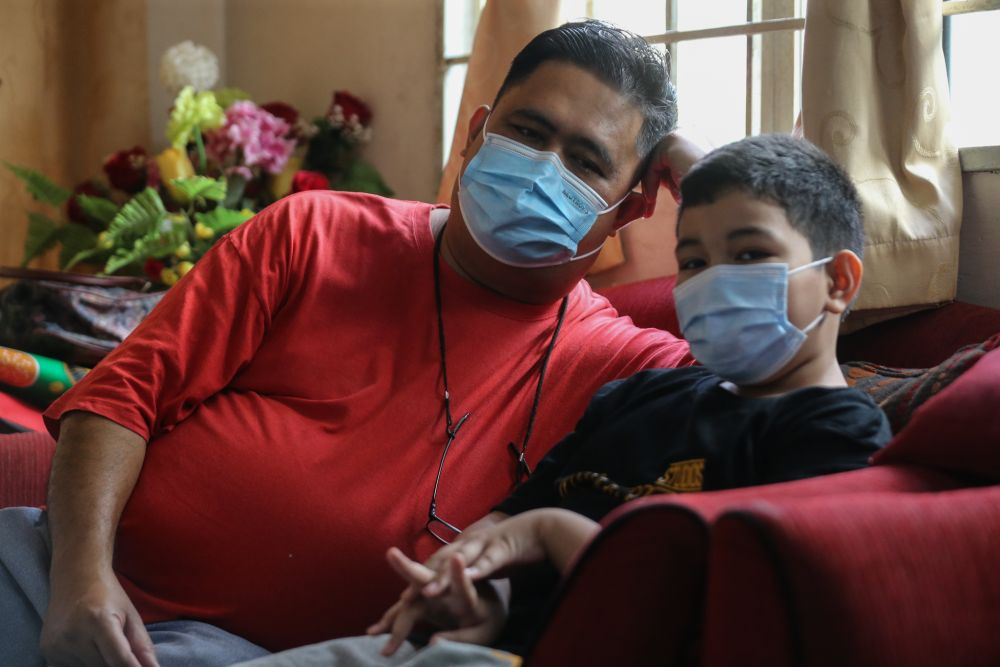 Rozaimi Rizal Mursal with his youngest nephew, Mohamad Faahil, who is nine. — Picture by Ahmad Zamzahuri