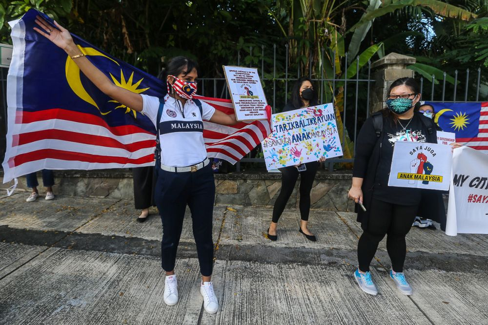 Malaysian mothers and members of Family Frontiers hold up placards demanding equal citizenship rights for Malaysians outside the Parliament building in Kuala Lumpur September 23, 2021. — Picture by Yusof Mat Isa