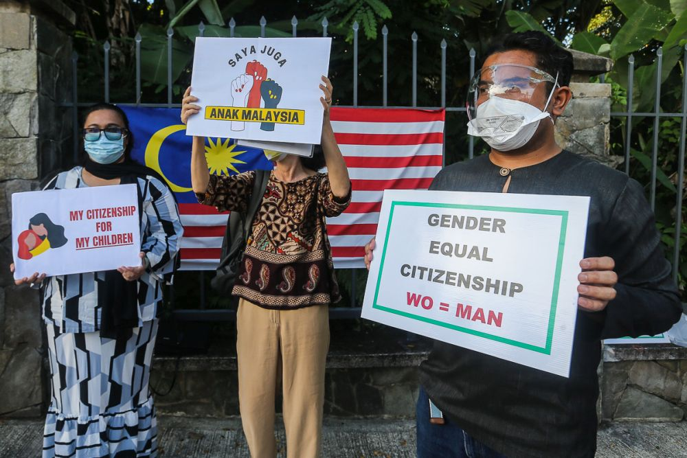 Members of Family Frontiers hold up placards demanding equal citizenship rights for Malaysians outside the Parliament building in Kuala Lumpur September 23, 2021. — Picture by Yusof Mat Isa