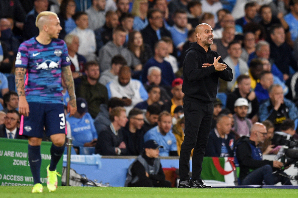 RB Leipzig defender Angelino looks on as Manchester City manager Pep Guardiola gestures from the sidelines during the Uefa Champions League 1st round Group A football match at the Etihad Stadium in Manchester, September 15, 2021. — AFP pic