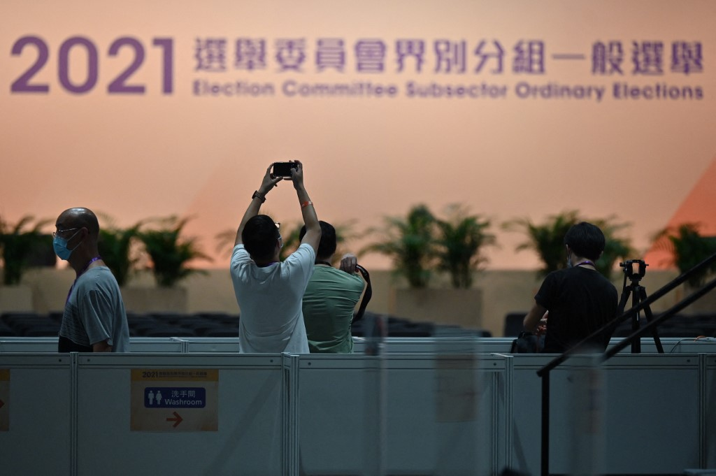 A journalist takes a photo inside the convention and exhibition centre in Hong Kong on September 19, 2021 where the political elite began selecting a powerful committee which will choose the city's next leader and nearly half the city's legislature under a new 'patriots only' system imposed by Beijing. — AFP pic