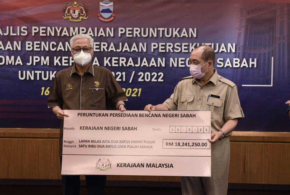 Prime Minister Datuk Seri Ismail Sabri Yaakob (left) hands over a mock cheque to Sabah Chief Minister Datuk Hajiji Noor in Kota Kinabalu September 16, 2021. ― Bernama pic