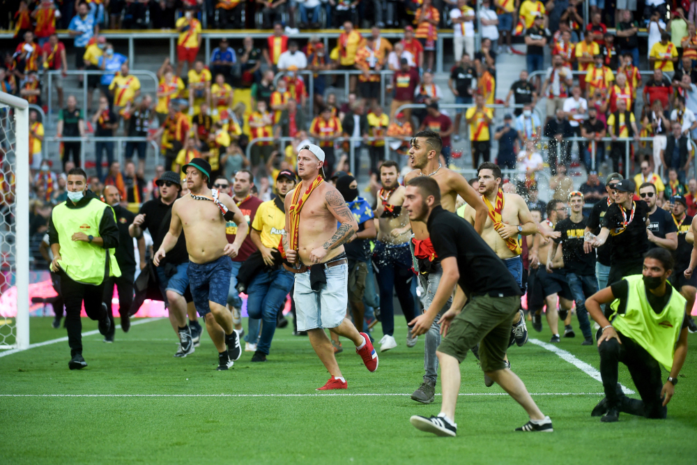 Lens' supporters invade the pitch during the French L1 football match between RC Lens (RCL) and Lille (LOSC) at Stade Bollaert-Delelis in Lens, northern France, September 18, 2021. — AFP pic