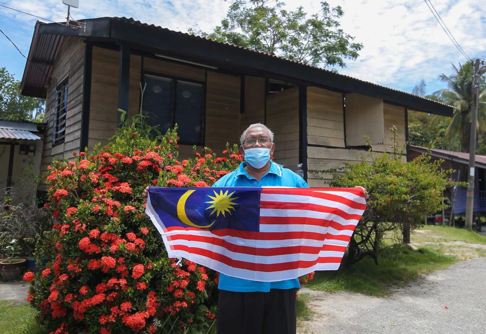 Tok Batin Anjang Alang poses with the Jalur Gemilang at Kampung Orang Asli Chadak, Ulu Kinta in Perak September 15, 2021. — Picture by Farhan Najib