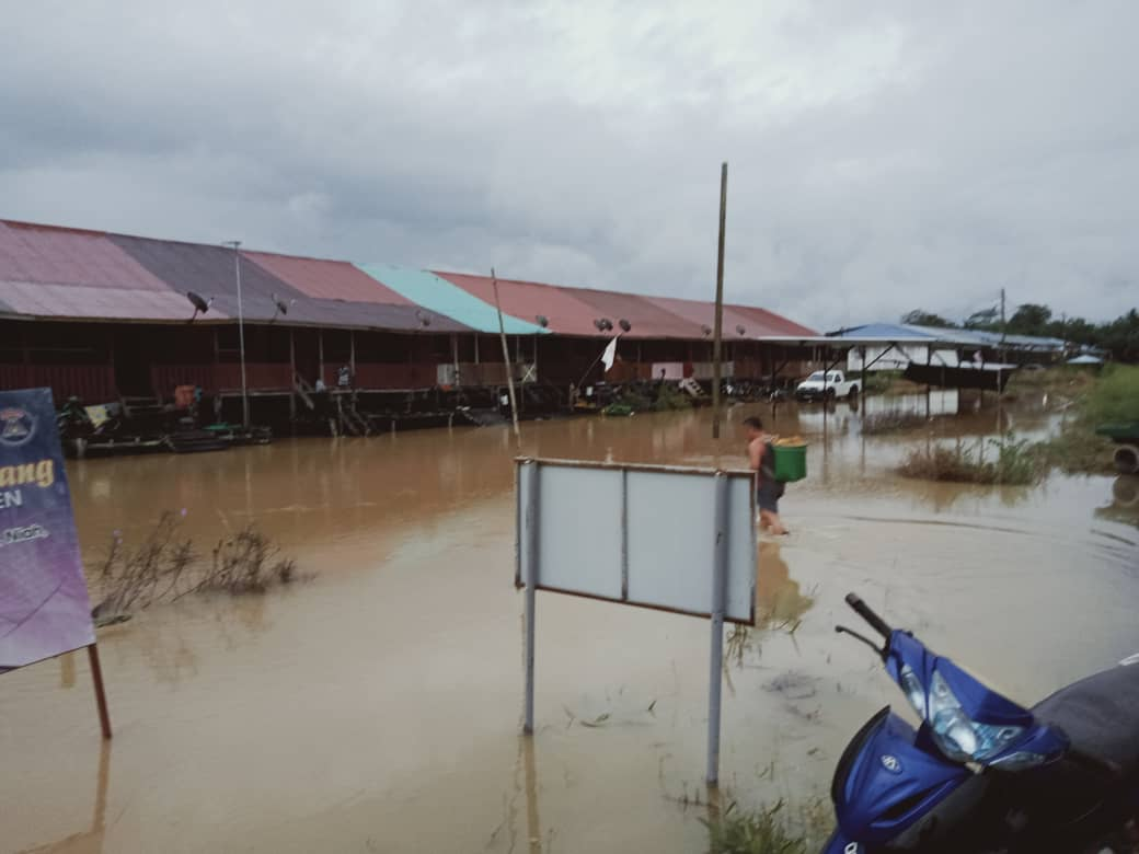 A resident walks through flood waters to Rumah Nelson Ningkan. — Picture courtesy of Miri Fire and Rescue Department
