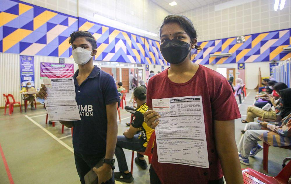 Siblings Rickneshwaran Govindasamy (left) and Tushalini Govindasamy show their vaccination cards after receiving their Covid-19 jab at the Kinta Town Hall in Batu Gajah September 21, 2021. — Picture by Farhan Najib