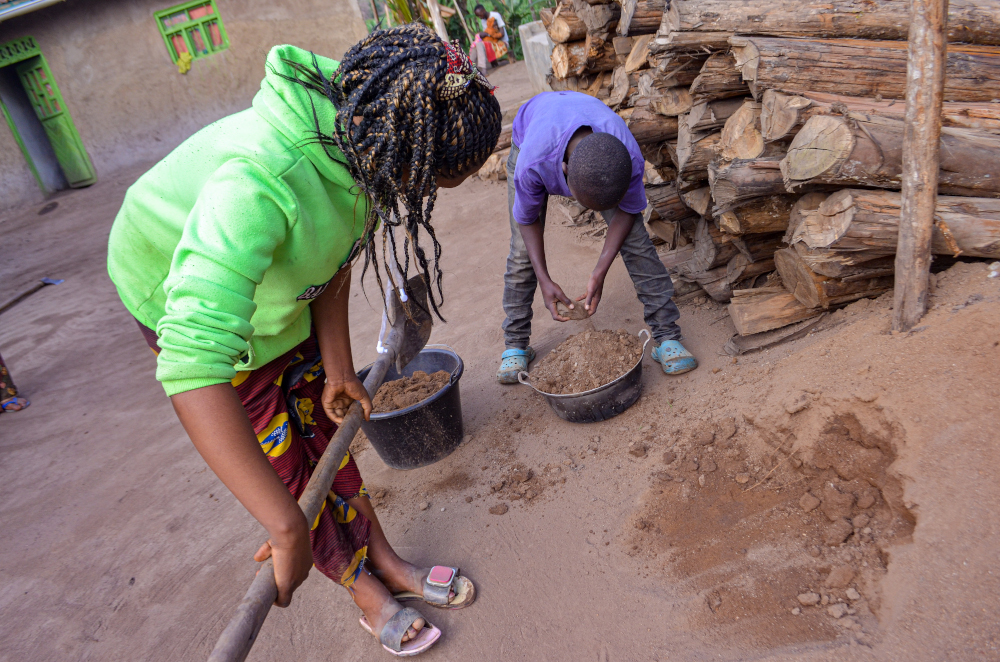 An Ebola orphan girl loads sand into a basin with her little brother in Butembo, Democratic Republic of Congo. August 26, 2021. — Djiress Baloki/Thomson Reuters Foundation pic