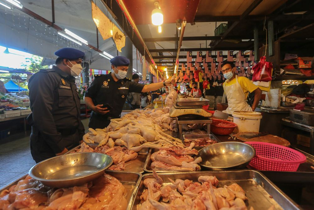 Domestic Trade and Consumer Affairs Ministry enforcement officers conduct checks on prices of chicken at Pasar Awam Moden Seksyen 6 in Shah Alam September 21, 2021. — Picture by Yusof Mat Isa