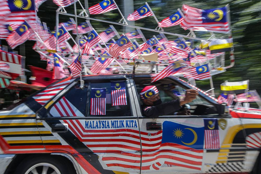 Tazar Alang Ibrahim, well-known among Ipoh folks for the Jalur Gemilang decoration on his iconic Proton Saga, takes to the streets August 23, 2021. — Picture by Farhan Najib