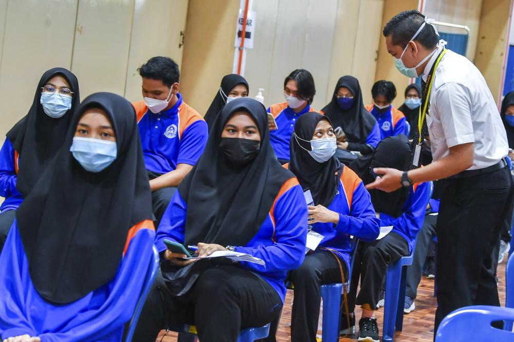 Health staff monitoring students in the observation section after receiving their Covid-19 vaccine at Sekolah Menengah Kebangsaan Putrajaya Precinct 8 (1), September 20, 2021. — Bernama pic