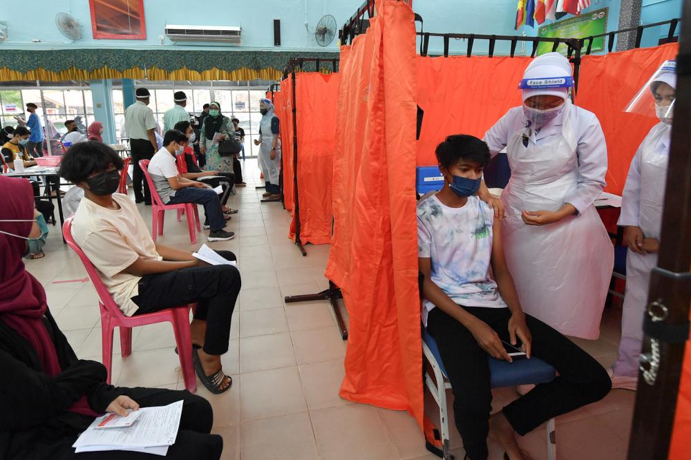 A health officer administers the Pfizer-BioNTech Covid-19 vaccine to a student at Sekolah Menengah Kebangsaan Sultan Sulaiman in Kuala Terengganu, September 21, 2021. — Bernama pic