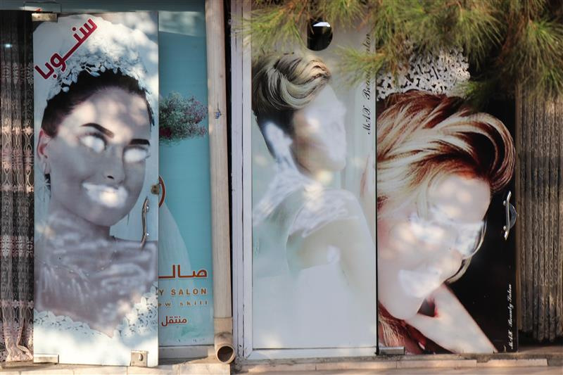 Images of women on a beauty salon in the Afghan capital Kabul are seen painted over in a photo taken in September 2021. — Thomson Reuters Foundation pic