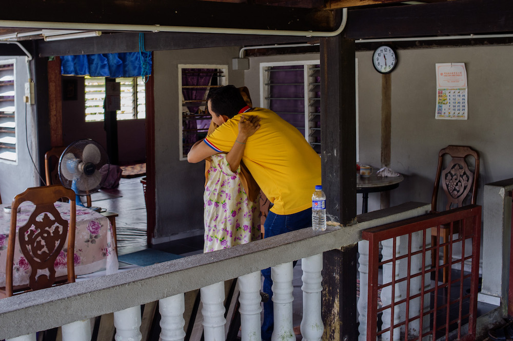 Taufik hugs his mother, Jamilah Damyati, after he made a surprise visit to his hometown in Bagan Datuk. — Picture by Shafwan Zaidon