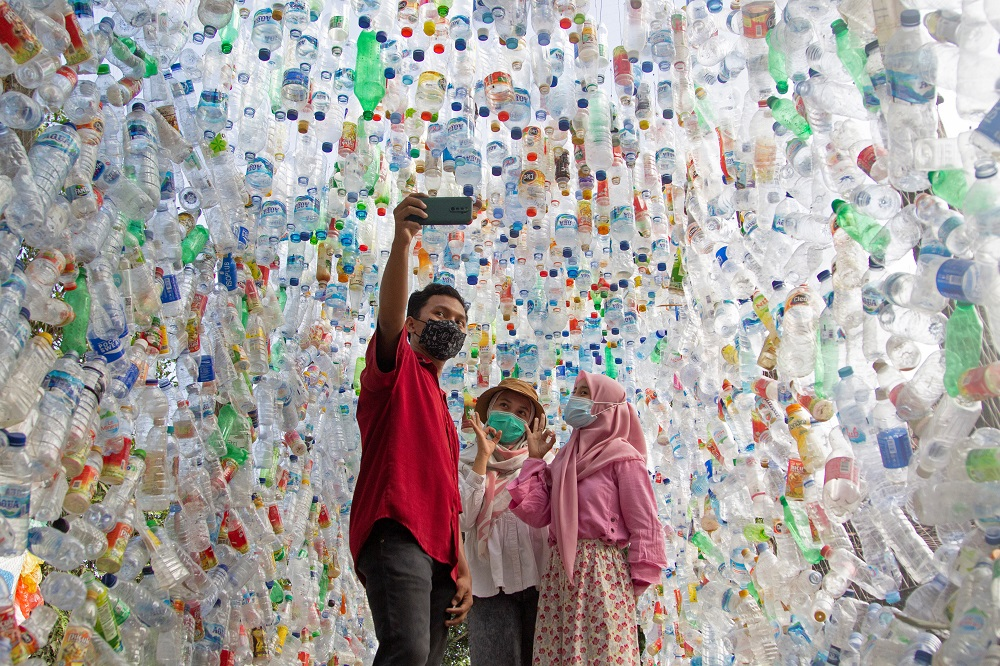 People take selfie pictures at 'Terowongan 4444' or 4444 tunnel at the plastic museum constructed by Indonesia's environmental activist group Ecoton in Gresik regency near Surabaya September 28, 2021. — Reuters pic
