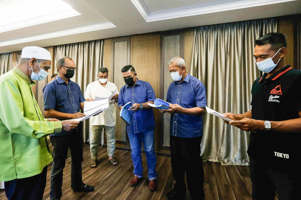Penang Fishermen Association Chairman Hamadi Md Rodzi (second left) along with South Penang Fishermen Association Chairman Arshad Omar (second right) and few other Fishermen Association reviewing the Minute Meeting booklet at Pen Mutiara, October 13, 2021. — Picture by Sayuti Zainudin