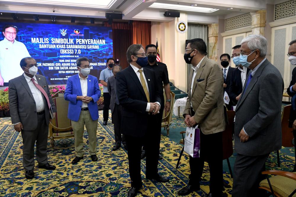 Sarawak Chief Minister Datuk Patinggi Abang Johari Openg speaks to an attendee of the symbolic handing-out of the BKKS 7.0 Plus at Wisma Bapa Malaysia in Kuching, October 14, 2021. — Bernama pic