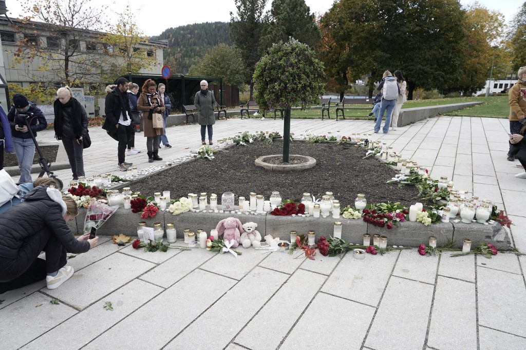 Inhabitants set up flowers and candles in the centre of Kongsberg, Norway, on October 14, 2021, the day after a man armed with a bow and arrows killed five people before being arrested by police. — AFP pic