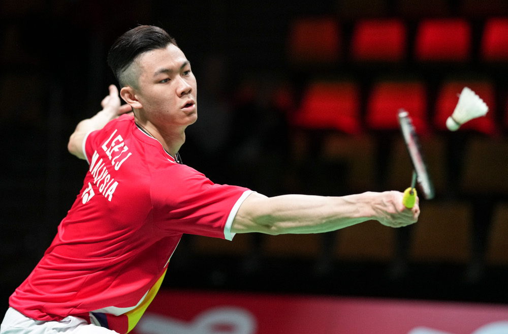Malaysia's Jia Lee Zii competes with Japan's Kento Momota (unseen) during a men's single match in the Thomas Cup men's team Badminton match between Japan and Malaysia in in Aarhus, Denmark, October 14, 2021. — AFP pic