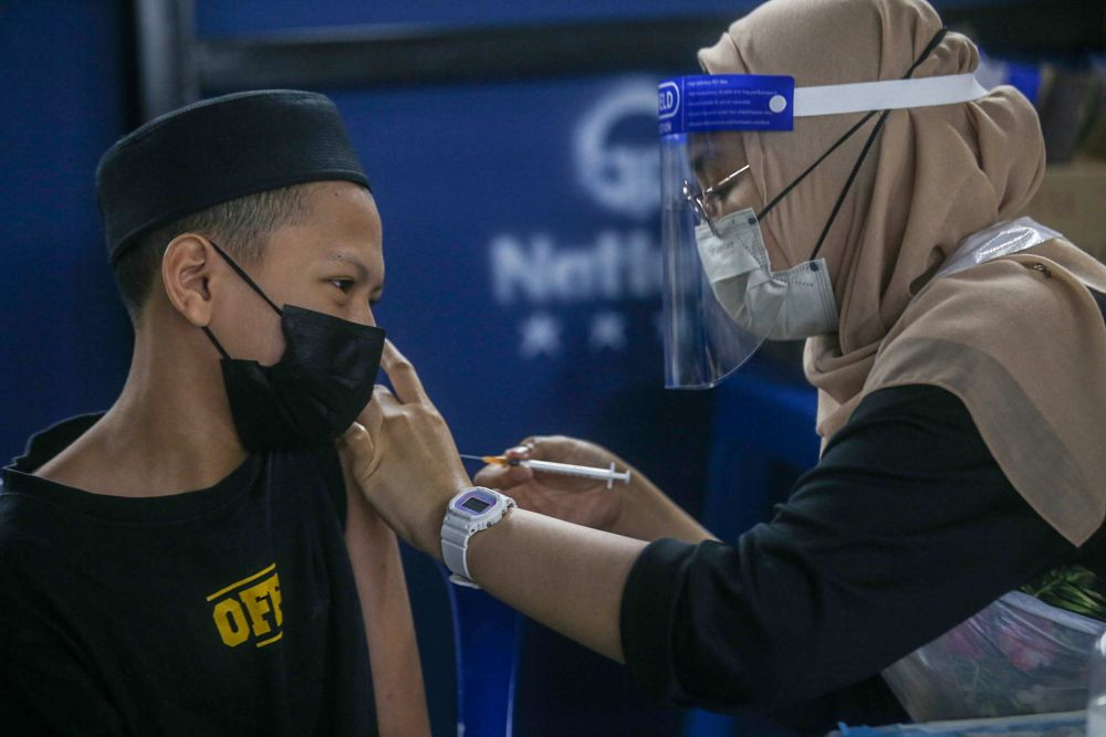 A student receives his Covid-19 jab at SMA Izzuddin Shah in Ipoh October 5, 2021. — Picture by Farhan Najib