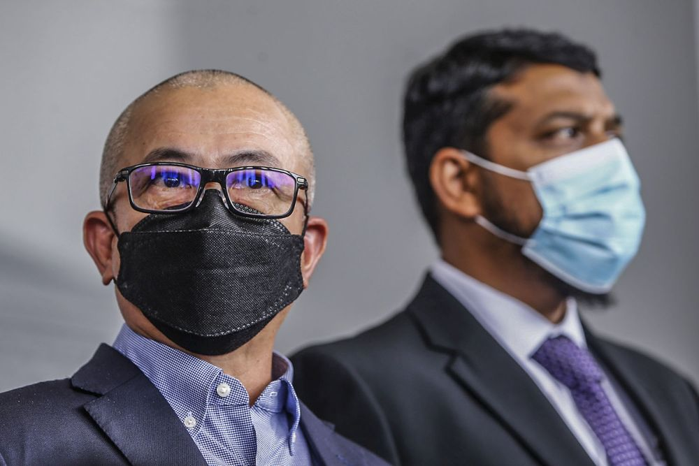 Labuan MP Datuk Rozman Isli is pictured with his lawyer Muhammad Rafique Rashid Ali (right) at the Kuala Lumpur High Court October 14, 2021. — Picture by Hari Anggara