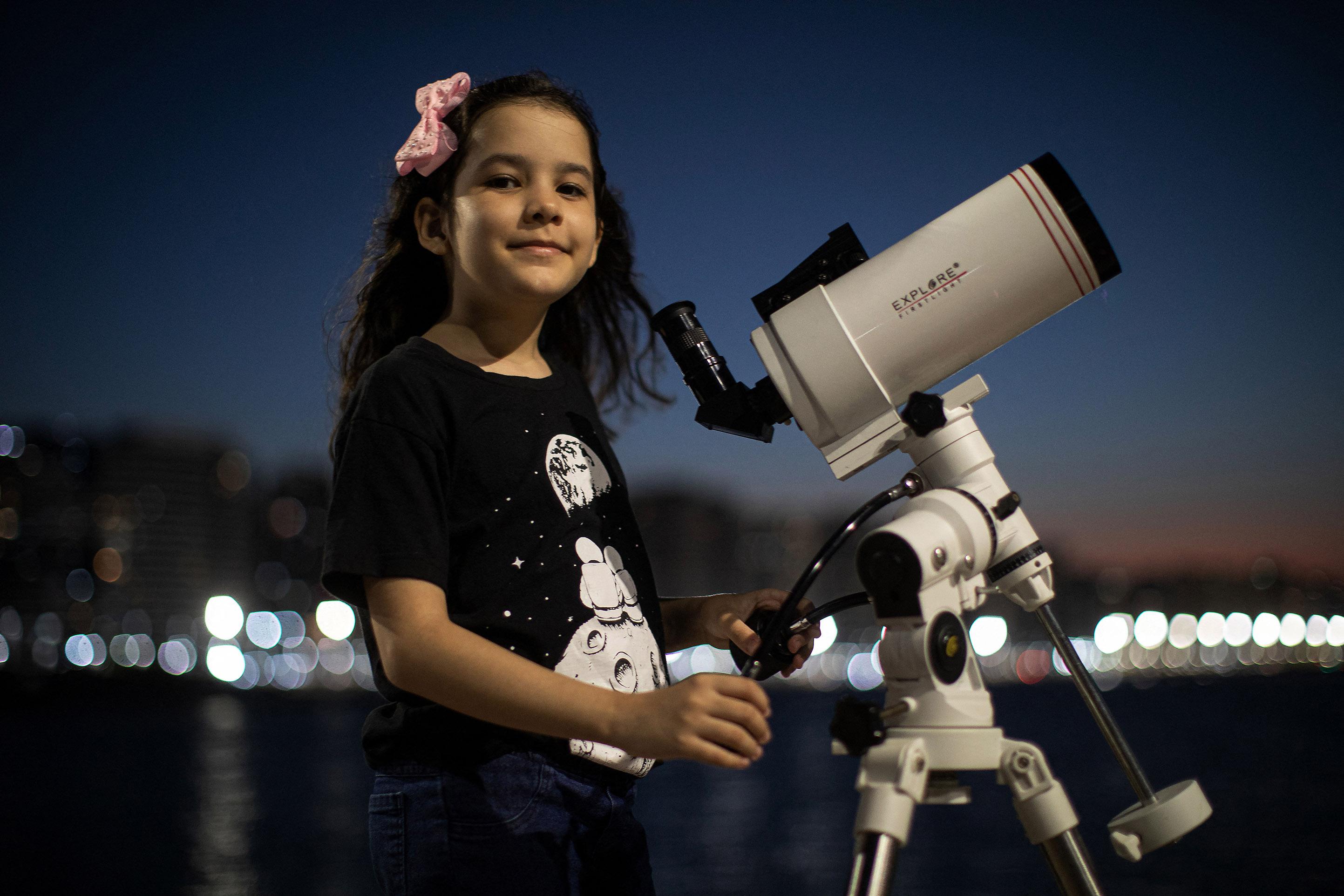 L'astronoma brasiliana di 8 anni Nicole Oliveira posa per una foto con il suo telescopio a Fortaleza, in Brasile.  - foto AFP