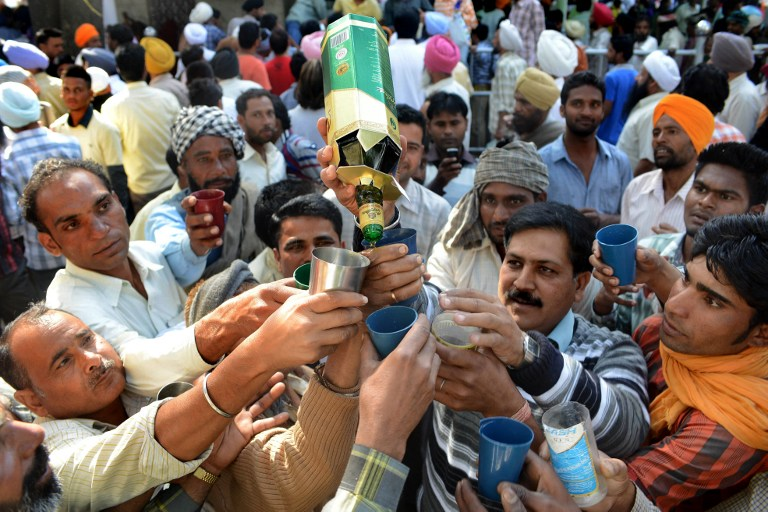 Indians distribute liquor in the village of Bhoma Wadala in this file photo taken March 24, 2013. — AFP pic