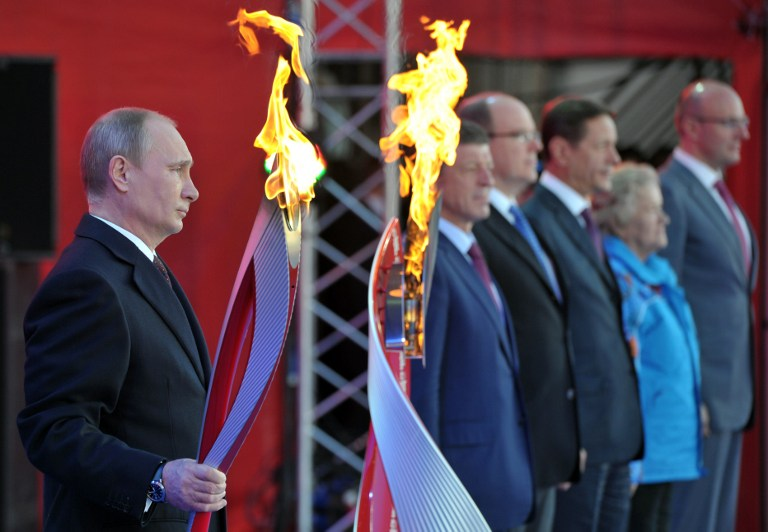 A file picture taken in Moscow on October 6, 2013, shows Russia's President Vladimir Putin holding a torch during a ceremony to mark the start of the Sochi 2014 Winter Olympic torch relay across Russia. — AFP pic
