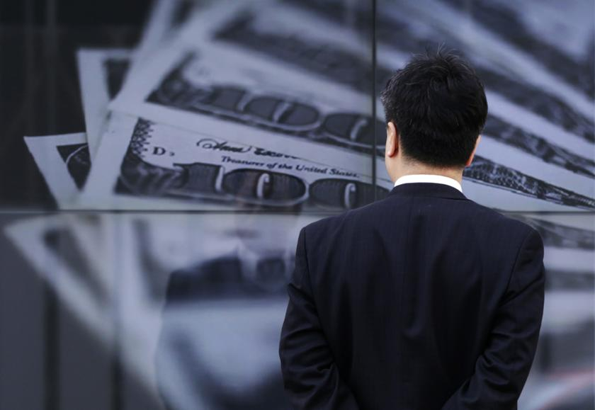 A businessman looks at a screen displaying a photo of 100 dollar bank notes, in Tokyo, in this April 8, 2013 file picture. — Reuters pic