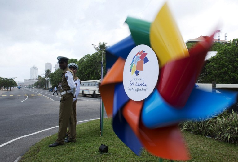 Sri Lankan police officers looks at a billboard featuring a windmill announcing the Commonwealth Heads of Government Meeting (CHOGM) in Colombo next week. —  AFP pic