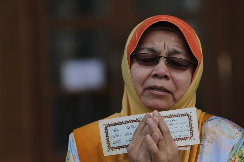 A Muslim woman recites a prayer during a demonstration outside Malaysia's Court of Appeal in Putrajaya, outside Kuala Lumpur October 14, 2013. — Reuters pic
