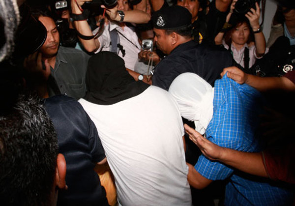 File photo of Azilah Hadri and Sirul Azhar Umar (heads covered) during one of their court appearances in 2009. — Picture by Choo Choy May