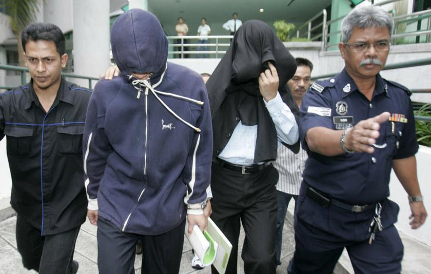 File photo of ex-policemen Azilah Hadri and Sirul Azhar Umar (heads covered). Sirul is considering revealing why he and another former police commando shot dead the Mongolian model and blew her body up with explosives. — Reuters pic