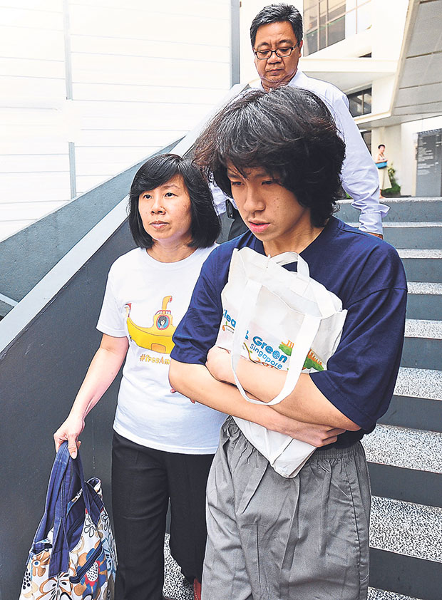 Singapore teenage blogger Amos Yee (R), accompanied by his mother Mary Toh Ai Buay (L) and father Alphonsus Yee (behind), walking out from the state court in Singapore on July 6, 2015. — Picture from AFP