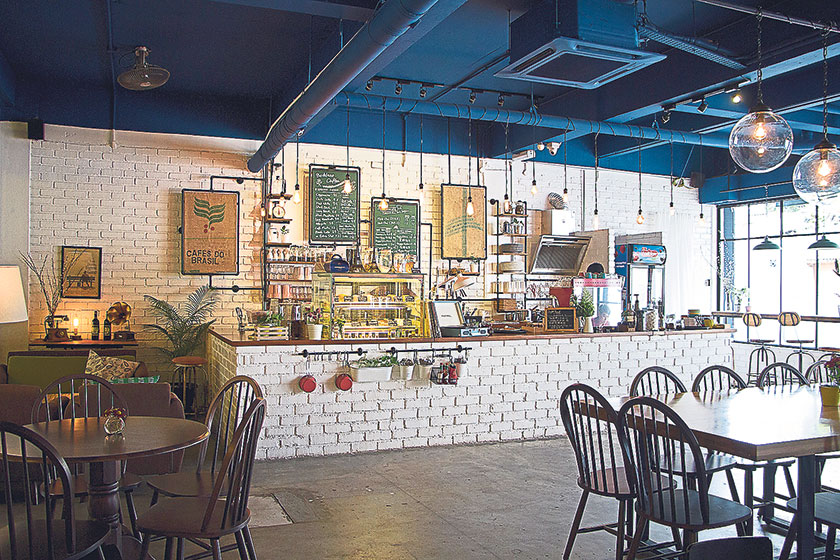 The long, white-bricked bar with a dessert display and an espresso machine humming away