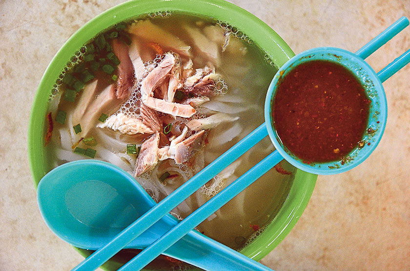 A heartwarming bowl of shredded chicken noodle soup with killer sambal belacan at Pokok Assam market to start the day with — Pictures by James Tan