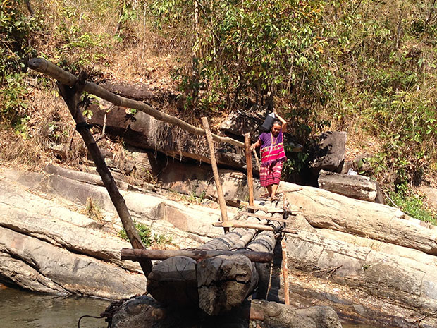 A Karen woman, dressed in a traditional outfit of handwoven fabric, makes her way carefully across a bamboo bridge.